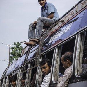 バスの屋根の上に座る青年