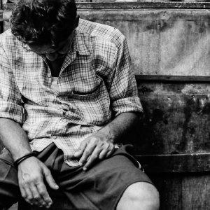 ベンチに座りながら寝る男