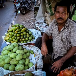 道端でマンゴーと柘榴を売る男