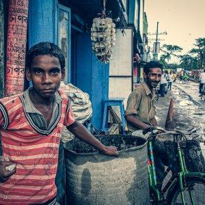 ドラム缶の横に立つ青年