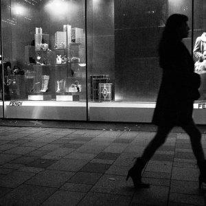 woman in high heels walking in front of a show window