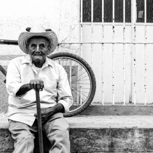 Old man with cowboy hat sitting by roadside