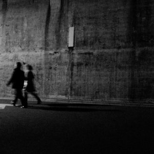 壁の前を歩く人影