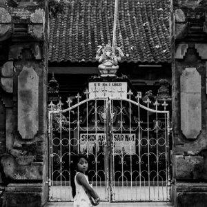 Girl walking in front of gate of school