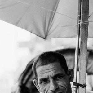 日傘の下で客待ちする男