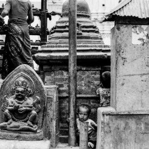 Boy playing among Buddha images