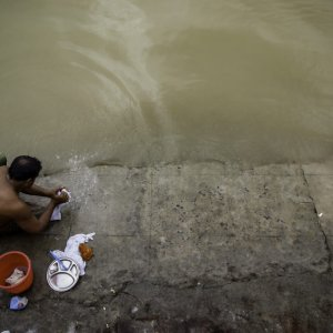 川で洗濯する男