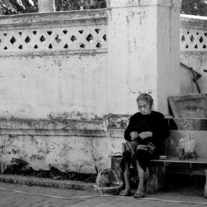 道端で裁縫する老婆