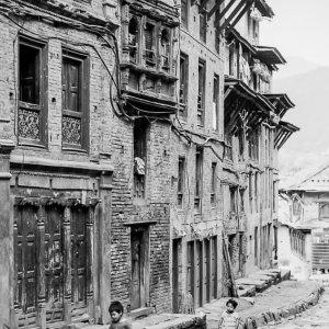 Boys walking stone-paved road