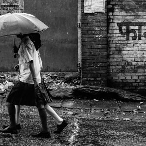 Two girls in rain with umbrella