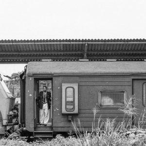 ゴール駅に停まる列車の乗降口に立つ男