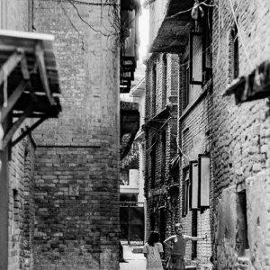 煉瓦造りの建物に挟まれた路地で立ち話をする女の子