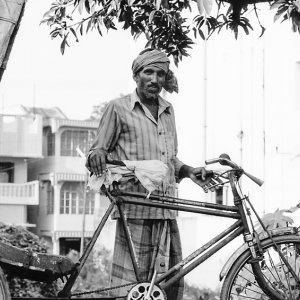 Man standing by cycle rickshaw
