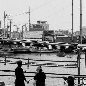 束草の港で漁網の手入れをする男と女