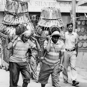 Men carrying metal container with Namlo and Doko