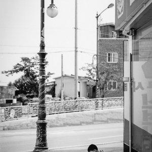 歩道で携帯ゲームをする男の子