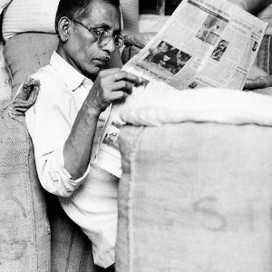 Man reading newspaper among hemp sacks