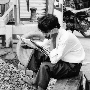 shoeless man reading newspaper