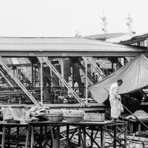 Man standing on roof of wooden boat