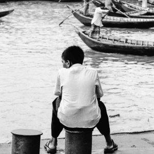 Boy sitting on bollard