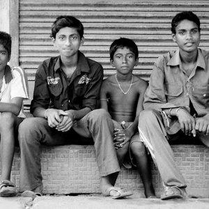 Four men sitting in front of shutter