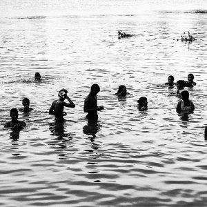 マハナンダ川に浸かる人びとのシルエット