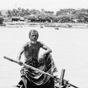 Oarsman holding bamboo pole