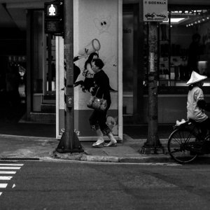 Woman with conical hat riding bicycle