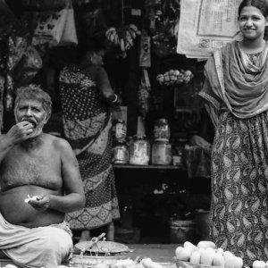 道端で食べる男と立つ女