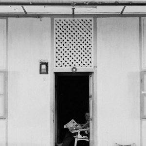 Man reading newspaper at entrance
