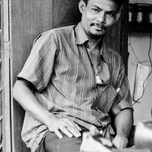 Man relaxing beside sewing machine