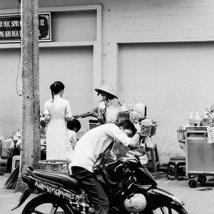 バイクの上で身嗜みを整える青年