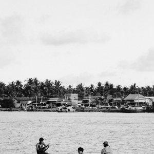 木製のボートに乗った三人