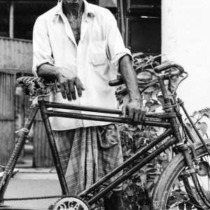 Man standing beside cycle rickshaw