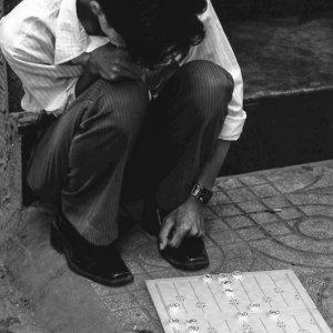 道端で中国将棋に興じる男