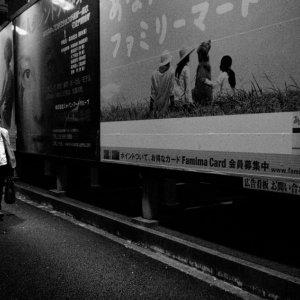広告の横を歩く男