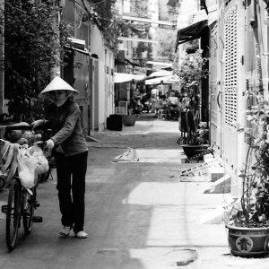Peddler walking bicycle in lane