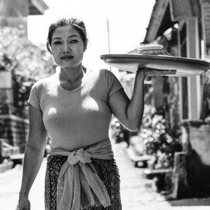 お供え物が載ったお盆を運ぶ女