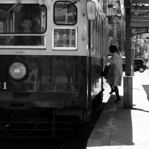 路面電車に乗り込む女