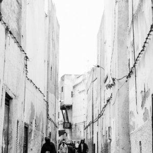 People walking alleyway without windows
