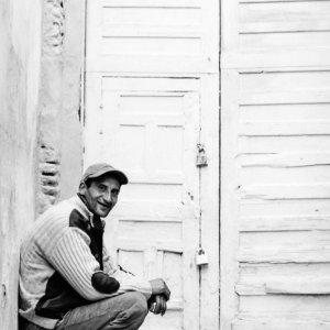 鍵の掛かった扉の前に座る男