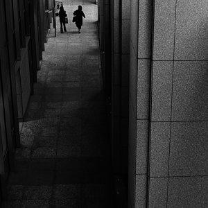 薄暗い通路を歩く人影のシルエット