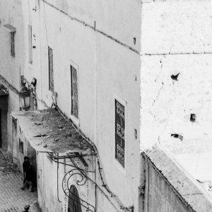 Figure walking in front of building