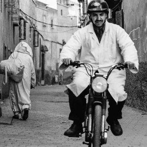 バイクに乗った白衣を着た男と路地を往くジュラバを着た男