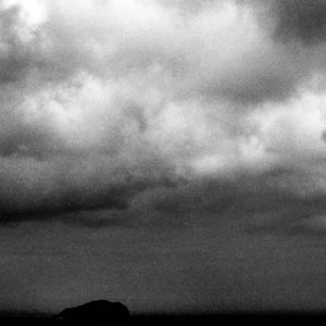 Silhouetted island on sea horizon