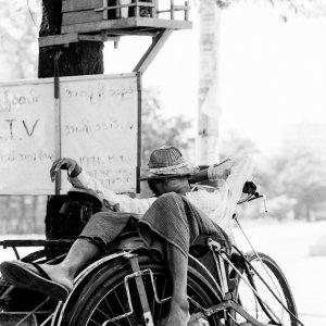 自転車タクシーの上で寝る男