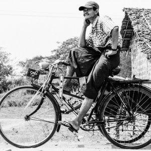 自転車タクシーの上でポーズを決める男