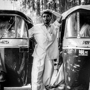 Man between auto rickshaws