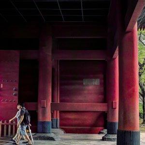 Worshipers walking under the red gate in Zojo-Ji