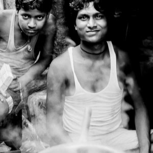 Men working at a chai stand and a steamy pot